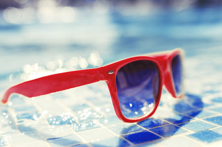 water s edge: Sunglasses next to a pool