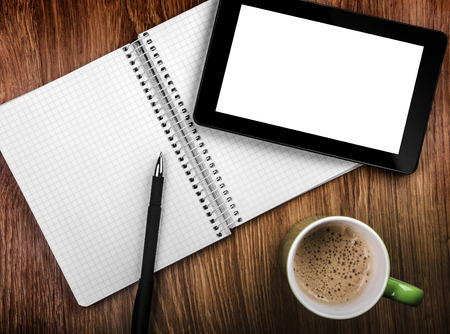 Tablet pc with an empty screen in hands close to a pen and green cup
