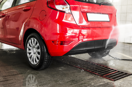 Red cars in a professional carwash station