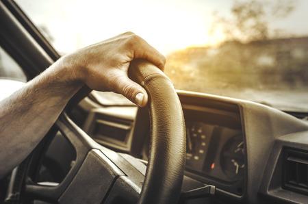 남자는 그의 차를 운전. 손 바퀴를 들고입니다. 톤의 사진입니다.