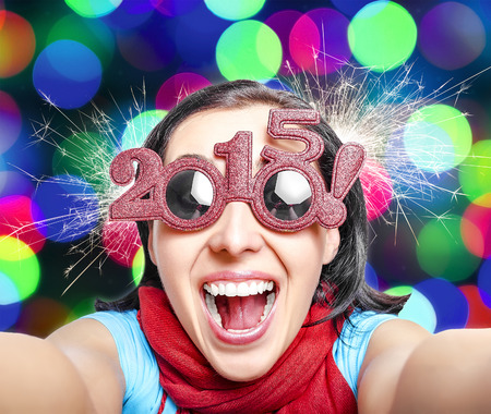 Two thousand and fifteen.  New Years concept. Girl in glasses  taking selfie.