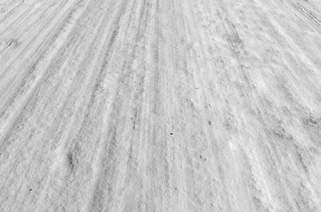 sidelit: Car tire track in fresh light snow