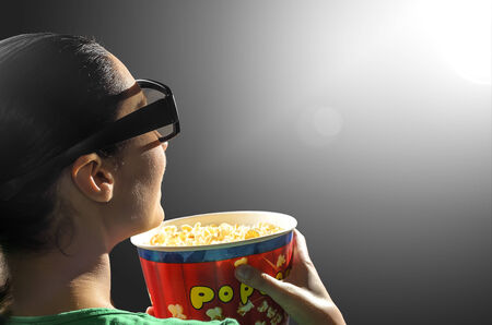 viewer: Girl watching 3D cinema in spectacles with bowl full of popcorn.