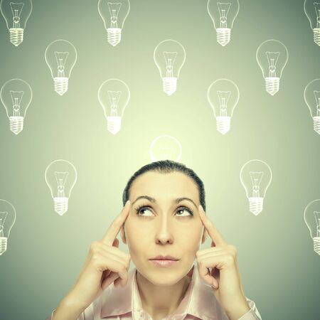 generates: Thinking woman looks up. Generates or produces the idea. Stock Photo