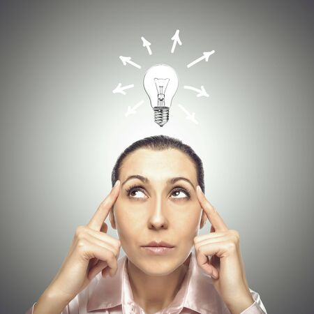 Thinking woman looks up. Generates or produces the idea. Stock Photo