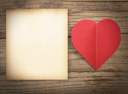 reciprocity: Red heart with sheet of paper on a old wooden board. Valentines Day concept. Stock Photo
