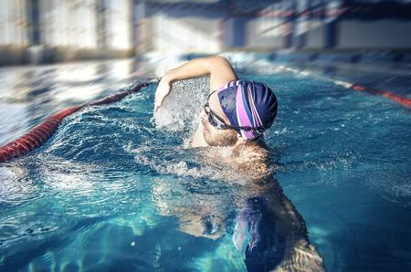 スイミング プールでクロール フリー スタイルをプロの水泳選手 写真素材