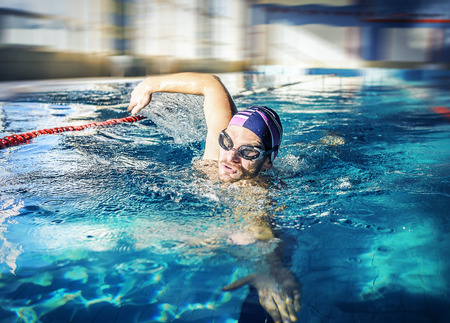 crawl: Young man swimming the front crawl in a pool