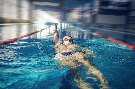 backstroke: Man swimmer swimming backstroke in blue water