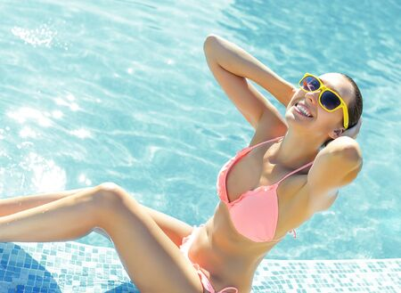 bathing   suit: Beautiful young woman standing in a swimming pool