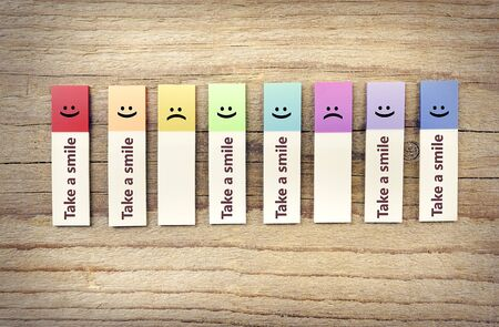 takings: Take smile ads. Colored paper stickers on a wooden background.