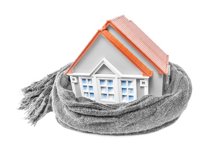 insulate: House wrapped in a scarf isolated on white. Conceptual image.