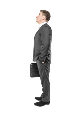 Businessman looking up with his hand in his pocket. Over white. photo