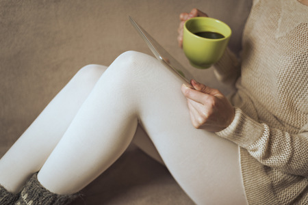 legwarmers: Woman on the sofa with tablet and cup of coffee in hands. Toned photo. Stock Photo