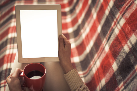 heated: Woman on the sofa with tablet and cup of coffee in hands. Toned photo. Stock Photo