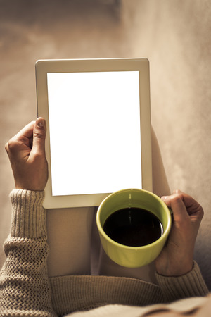 Woman on the sofa with tablet and cup of coffee in hands. Toned photo. Standard-Bild