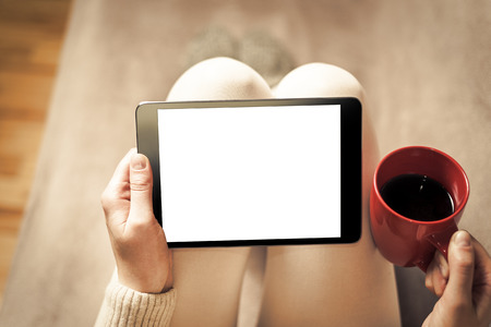 Woman on the sofa with tablet and cup of coffee in hands. Toned photo. 스톡 콘텐츠