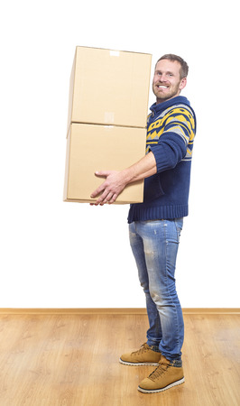 first time buyer: Man with box moving into new room and smiling