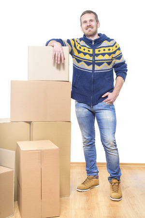 first time buyer: Man packing boxes getting ready to move in empty room. Stock Photo