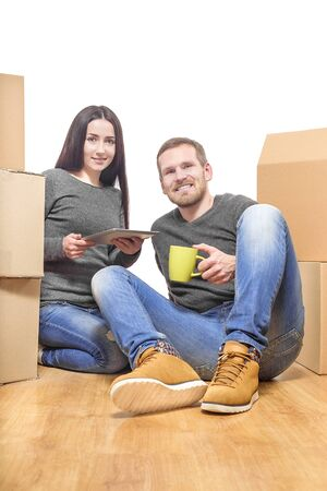Couple in new home between the boxes, with a cup and Tablet PC in the hands. photo