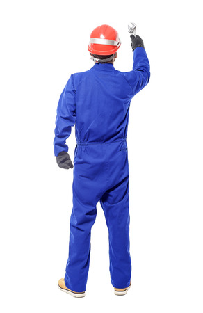 overalls: A back view of a worker holding a wrench isolated on white background.