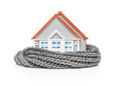 economizing: House wrapped in a scarf isolated on white. Conceptual image.