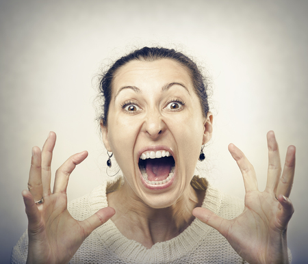 ugly woman: Furious woman screaming. Front view of furious brunette woman yelling at camera.