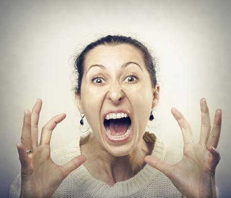 mujer fea: Mujer furiosa gritando. Vista frontal de la mujer morena furiosa gritando a la cámara. Foto de archivo