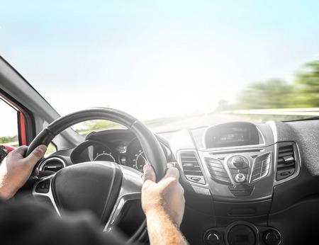 Kierowca jazdy nowoczesny samochód na drodze na zachód słońca. Widok z kokpitu. Zdjęcie Seryjne