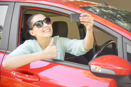 happy customer: Smiling young woman taking selfie picture with smart phone camera outdoors in red car.