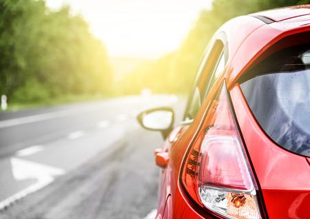 carretera: Coche rojo en la carretera al atardecer.