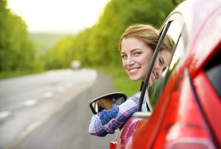 chofer: Muchacha sonriente feliz en un coche rojo. Al atardecer. Concepto del recorrido.