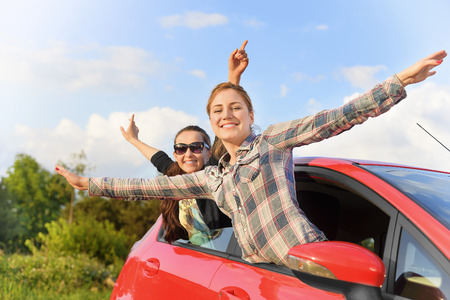 Happy beautiful young girls in a red car in the sunset. Travel concept. photo