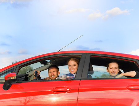Friends in a red car. Travel freedom concept. photo