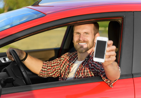 Man in car driving showing smart phone display smiling happy. Focus on model. Stock Photo - 40213033