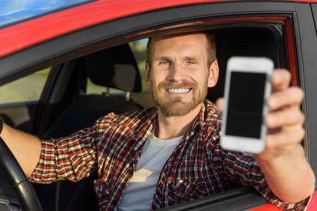 beau jeune homme: Homme dans la voiture conduite montrant l'�cran du t�l�phone intelligent sourire heureux. Focus sur mod�le.