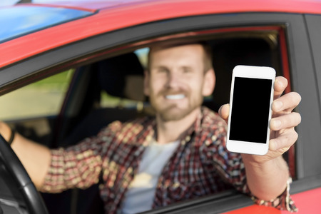 Man in car driving showing smart phone display smiling happy. Focus on smartphone.