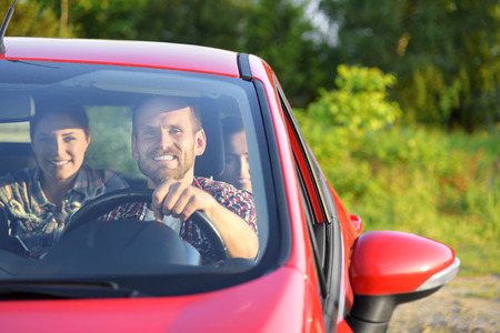25 30 years: Friends in a red car. Travel freedom concept. Stock Photo