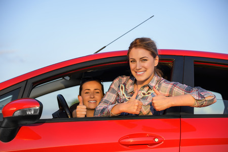Happy beautiful young girls in a red car in the sunset. Travel concept. Stock Photo