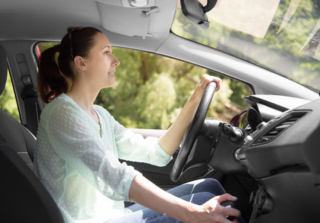 Attractive woman driving her car. Side view. photo