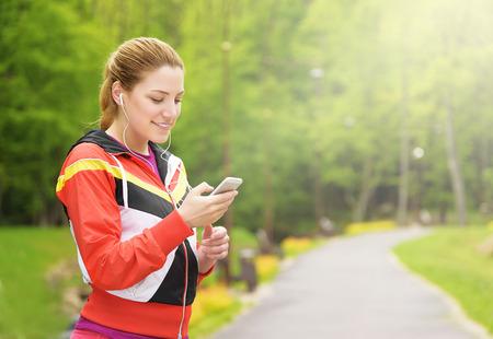 escucha activa: Trotar mujer joven en un camino del parque que tiene descanso y escuchar música. Foto de archivo