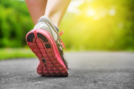 Dames benen in schoenen op runner joggen in het park bij zonsondergang.