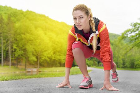 Attractive blonde woman running on track outdoors fitness, sport, training and lifestyle concept.