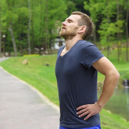 실행 한 후 피곤하고 지쳐 휴식 주자입니다. 산악 도로에 야외에서 훈련 도중 휴식을 취하기 조깅 남자.