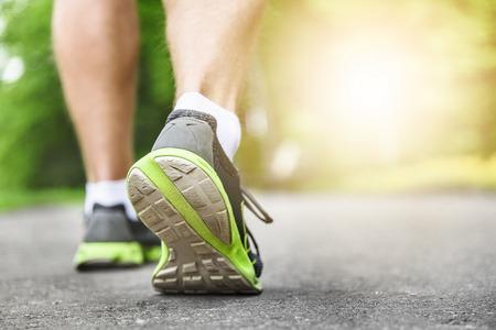 salud y deporte: Pies corredor atleta que se ejecutan en primer plano de carreteras en el zapato. fitness mujer amanecer jog entrenamiento concepto de bienestar.