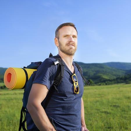 attractive male: Caminante masculino atractivo en la ladera en la puesta del sol.