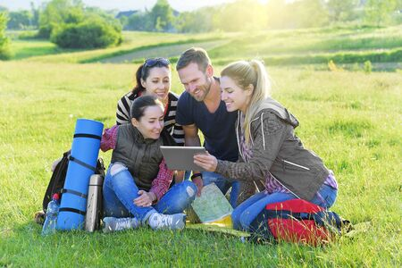 Group hikers on the grass with backpack used tablet pc, summer outdoor. Adventure, travel, tourism, hike and people concept. photo