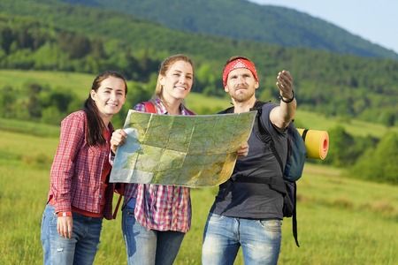 Young friends tourists with map in the park. Adventure. photo