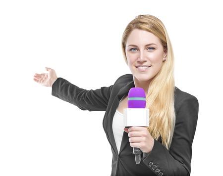 Aantrekkelijke blonde tv-presentator met een microfoon en wijst op een object. Geïsoleerd op een witte achtergrond.