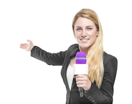 Attractive blonde TV presenter holding a microphone and points to an object. Isolated on white background.